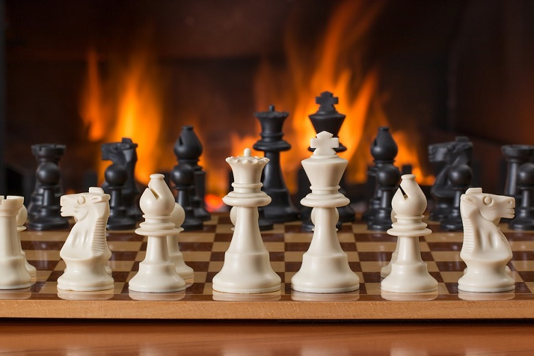 Chess placed on the board against the backdrop of a blazing fireplace